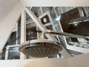 Showerhead under ancient photographs of Anton Pieck's bakery