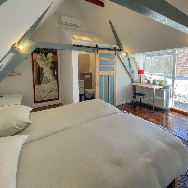 Lichte kamer met balkenplafond, houten vloer, een groot bed, een eigen badkamer, een bureau, stoel en toegang tot de eigen badkamer, evenals tot het dakterras
