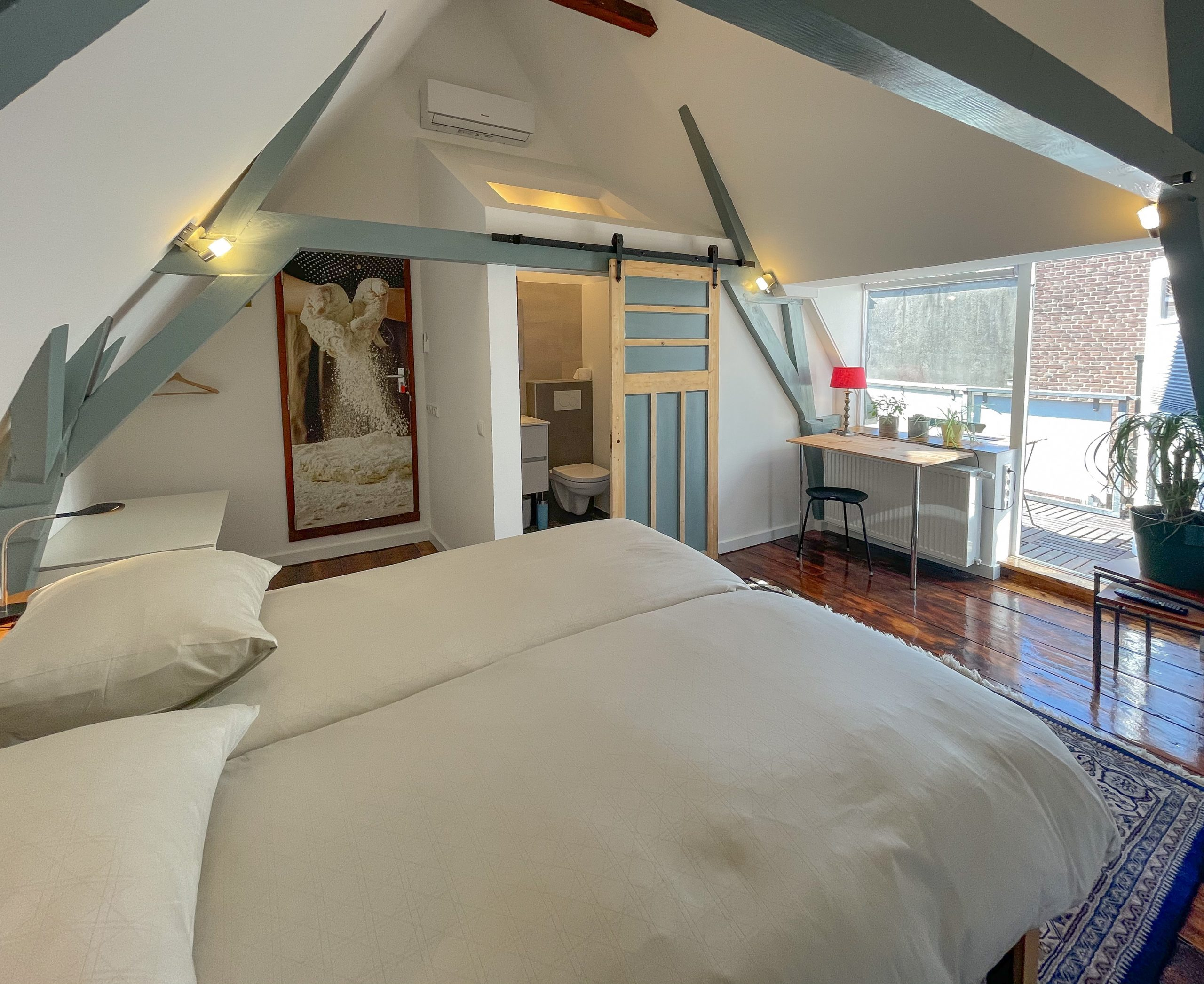 Light room with exposed beams, wooden floor, one large bed, a private bathroom, a desk, chair and access to the private bathroom, as well as to the roof terrace