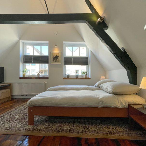 Lichte kamer met balkenplafond, een houten vloer, TV, groot tapijt en groot bed. De zon komt binnen door twee grote ramen.