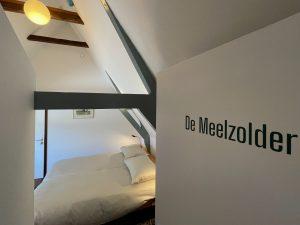 De Meelzolder: Een lichte kamer met balkenplafond en een groot bed