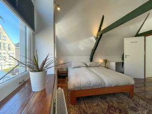Light room with exposed beams, a wooden floor, a large carpet and a large bed. The sun enters from two big windows