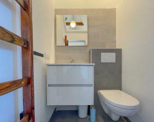 Eigen badkamer met een toilet, wastafel en spiegel