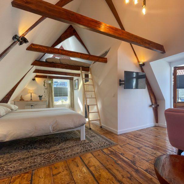 Lichte kamer met balkenplafond, houten vloer, en twee grote bedden, waarvan een toegankelijk is via een ladder. Er is een bank en TV op de achtergrond, evenals toegang tot het dakterras