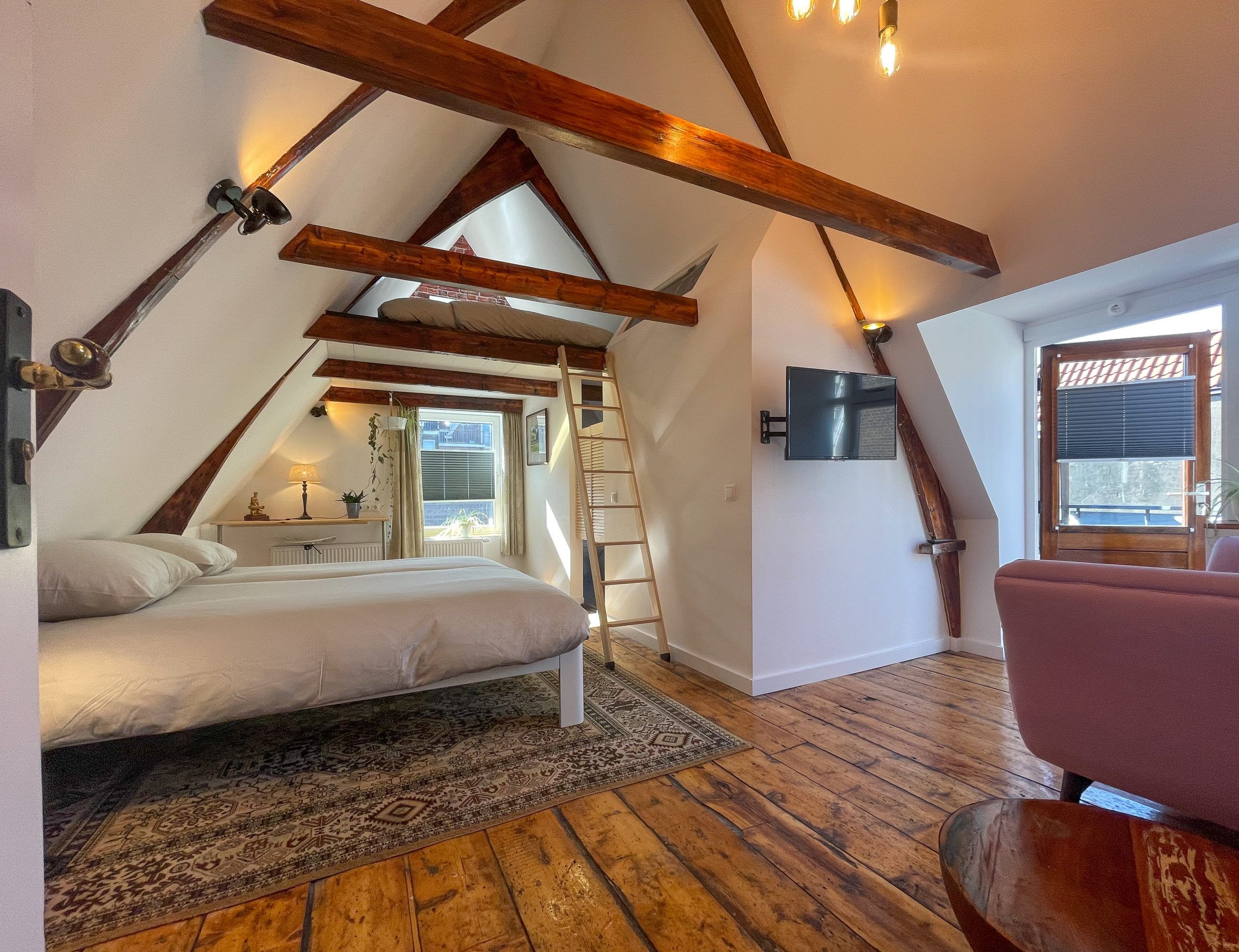 Light room with exposed beams, wooden floor, and two big beds, of which one is accessable via a ladder. There is a sofa and TV in the background as well as access to the roof terrace